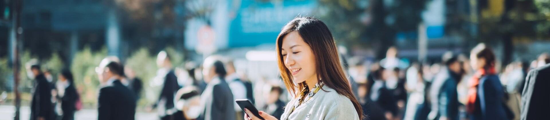 Asiatisk kvinna som tittar på mobil